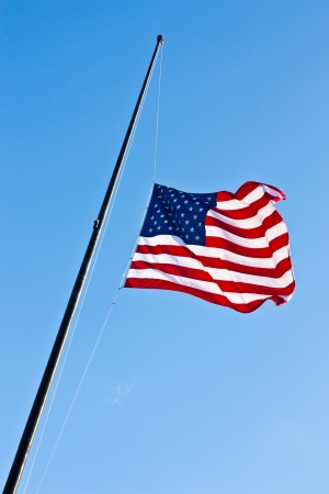American flag on a blue sky during a windy day photo