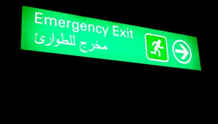 Emergency exit sign in an international airport in Middle East with Arabic information