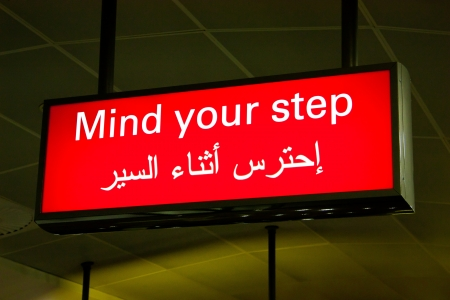 Mind your step sign in an international airport in Middle East with Arabic information photo