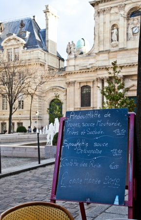Black board with a menu restaurant in a tipical traditional square in Paris photo