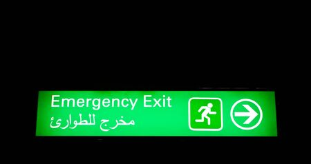 Emergency exit sign in an international airport in Middle East with Arabic information photo