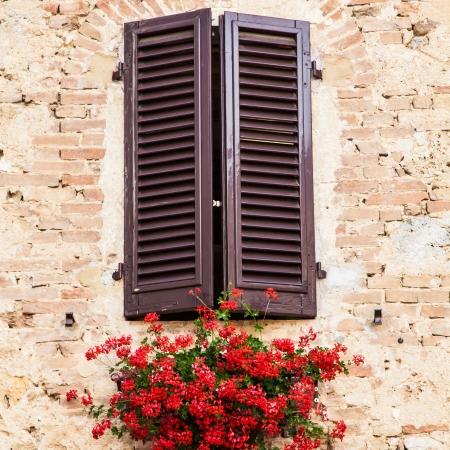 Toscaanse ramen met rode bloemen Oude muur op de achtergrond Stockfoto