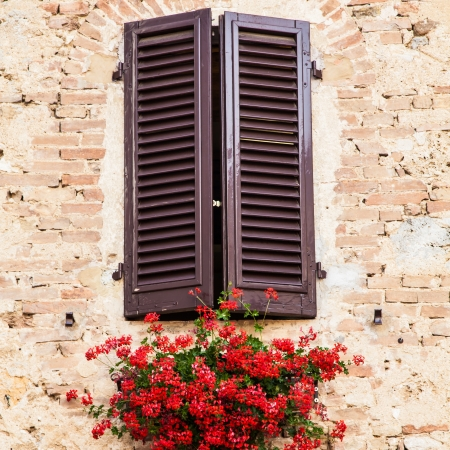 Tuscan windows with red flowers  Old wall in background