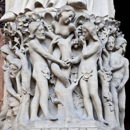adam: Detail on Notre Dame de Paris Cathedral fachade: Adame, Eve and the forbidden apple Editorial