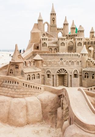 夏の日中にビーチにグランド砂の城