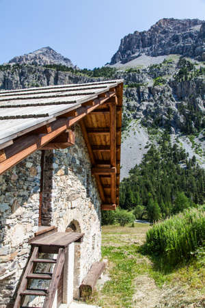 Swiss Alps, mountain cottage made of stone and wood, summer season photo