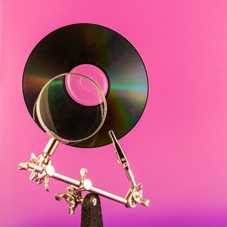 Concept for data analysis, CD and lens on a vivid colors background photo