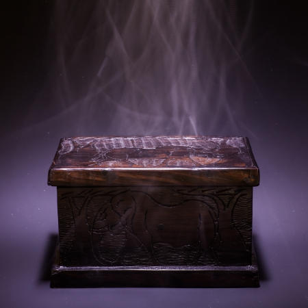 Ancient African box made of wood with light from the top and smoke effect photo