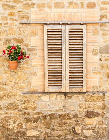 Pienza, Tuscany region, Italy. Old window with flowers photo
