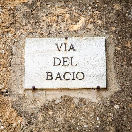 Italy - Pienza town. The streetsign of Via del Bacio (Kiss Street)