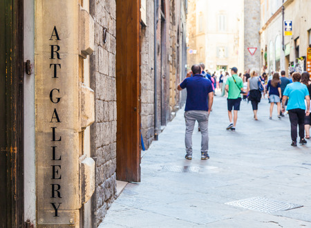 turism: Tuscany, Italy. An art gallery signseen in a street full of turism.