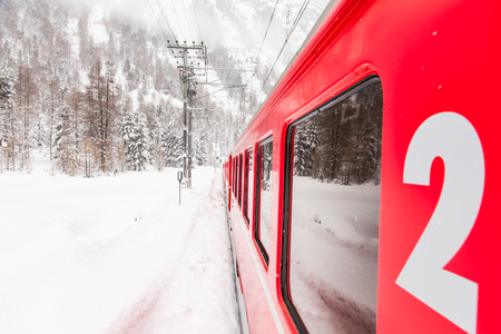 A red train in the middle of a desert of snow photo