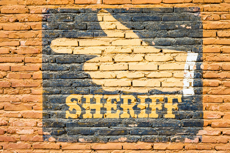 Sheriff graffiti on an old brick wall. Concept for security