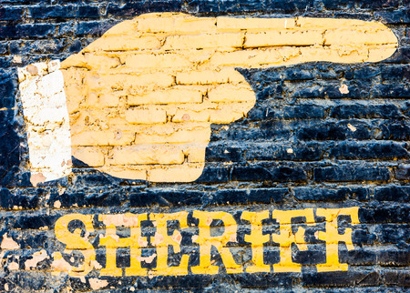 Sheriff graffiti on an old brick wall. Concept for security photo