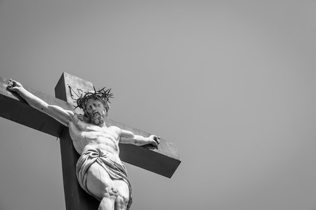 praying at church: Crucifix made of marble with blue sky in background. France, Provence Region. Stock Photo