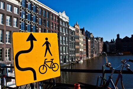gabled houses: Amsterdam canal view with sign for bicycle, close to the center of the city