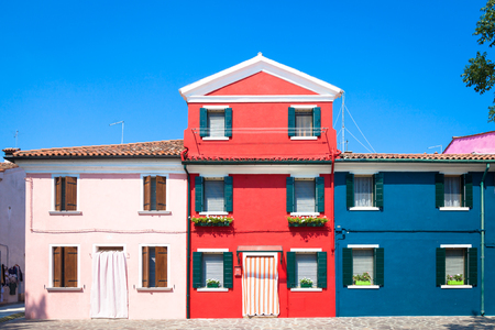 Burano Isle, close to Venice. Traditional colored houses during a sunny day.