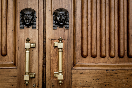 misterious: Detail of two bronze Sphinx heads on an old wooden door - around 100 years old, Italian palace in North Italy Stock Photo