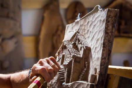Detail of caucasian middle aged scultor working on wood, natural daylight Stock Photo