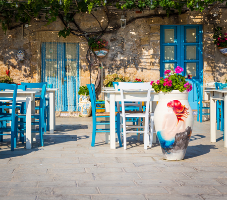characteristic: Tables and chairs setup in a traditional Italian restaurant in Marzamemi - Sicily during a sunny day