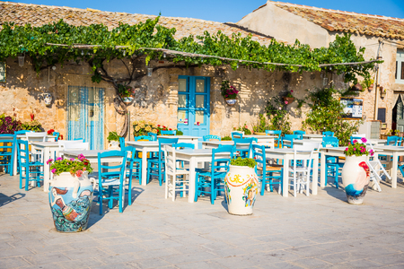 Tables and chairs setup in a traditional Italian restaurant in Marzamemi - Sicily during a sunny day Stok Fotoğraf - 90276454