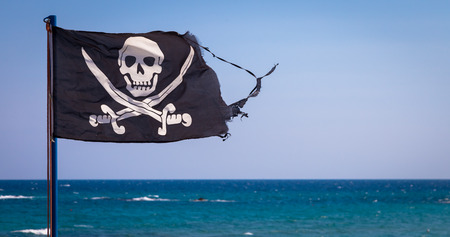 A damaged pirate flag during a strong windy day