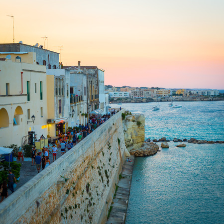 At peak of turistic season, the turist crowd is walking at sunset on the road from the new to the old side of Otranto town
