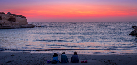 Three women waiting for the sunrise in front of the sea (Puglia region, South of Italy). Concept of frienship, travel and adventure. Stock Photo
