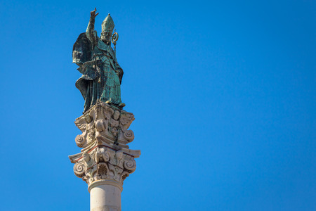 The symbol of Lecce town (Italy): Saint Oronzo (SantOronzo) posed on the column at the center of the main town Square. Blue backgroud with copy space.