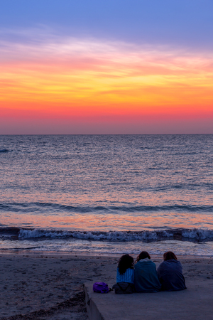 Three women waiting for the sunrise in front of the sea (Puglia region, South of Italy). Concept of frienship, travel and adventure. 版權商用圖片