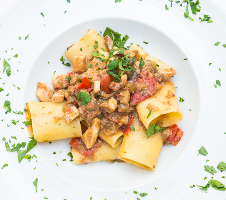 Otranto town, Puglia Region, South of Italy. Traditional Paccheri pasta with Swordfish, served with tomato, parsley, olive oil. Daylight, real restaurant in Otranto. Reklamní fotografie