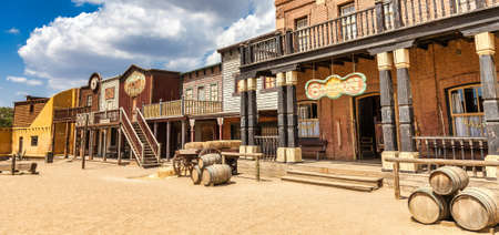 ALMERIA, SPAIN - CIRCA AUGUST 2020: Vintage Far West town with saloon. Old wooden architecture in Wild West with blue sky background.