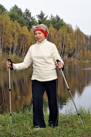 sportswoman: Senior woman train nordic walking