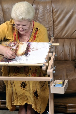 Woman embroidering a picture (cross stitch)