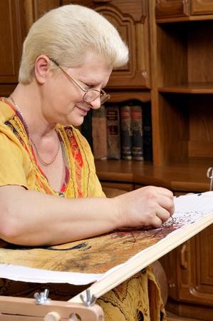 Vrouwen borduren een foto (cross stitch)