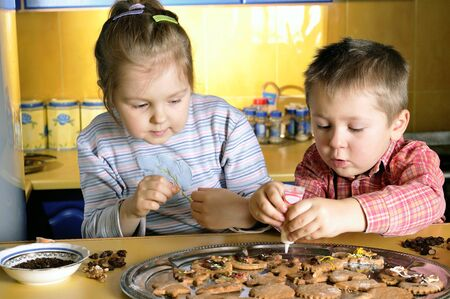 Young girl and little boy create cookies