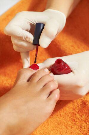 Woman applying red nail polish