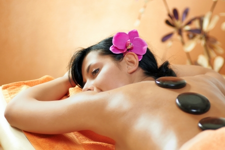 Woman getting a hot stone massage at spa salon photo