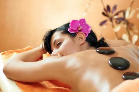 massage stones: Woman getting a hot stone massage at spa salon