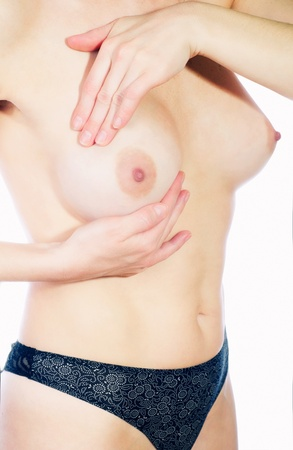 adult woman examining her breast for lumps or signs of breast cancer Stock Photo - 12583904