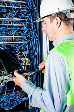 engineer in network server room solving problems photo