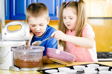 Young boy and girl making chocolate muffins photo