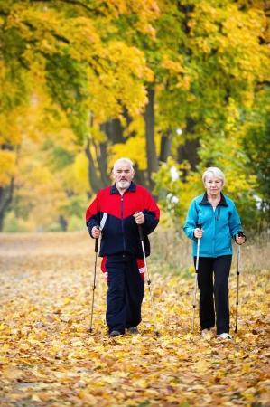 senior paar het maken van nordic walking in het park