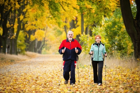 senior couple making nordic walking in the park