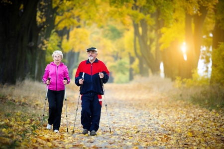 pasear: pareja de ancianos haciendo n�rdicos caminando en el parque Foto de archivo