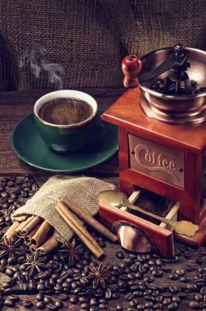 winnower: hot cup of coffee and fresh coffee beans and coffee grinder