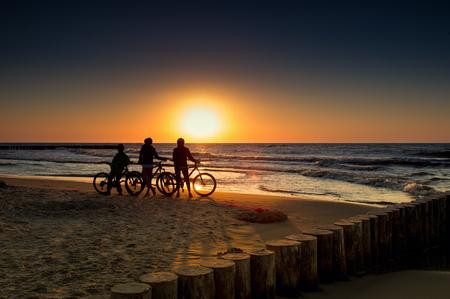 Gezin met fietsen op de Baltische Zee bij zonsondergang