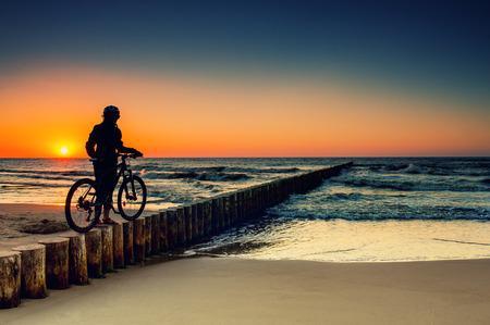Vrouw met fietsen op de Baltische Zee bij zonsondergang