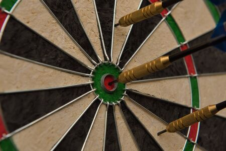 One of three darts hits the center of the darts board also known as Фото со стока