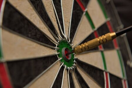 A dart hits the center of the darts board also known as Banque d'images